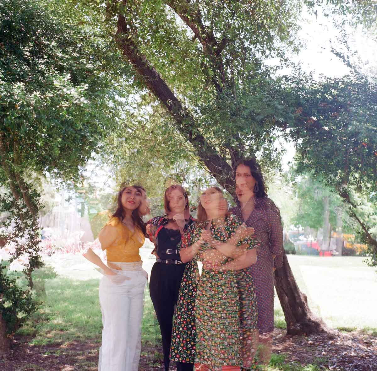four women standing in the middle bottom of the image in front of a tree leaning diagonally from the bottom right corner to the top left. the image is slightly out of focus giving the impression of multiple images gauzily overlaid on top of each other.