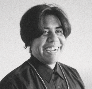 b&w photograph; Patrick Kelly, AKA Hope, looks into the bottom right corner of the frame laughing. his mid length hair is parted down the middle and flops over this round cheeks. he is wearing a dark shirt buttoned all the way up with a long beaded necklace falling out of frame over this chest.
