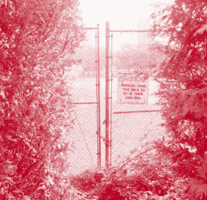"red and white image. a chained gate is centered between 2 bushes. on the right side there is a notice that reads ""NOTICE. PERSONS USING THIS WALK DO SO AT THEIR OWN RISK"""