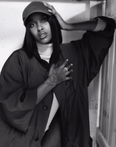 Samira Warsame, AKA ZamZam, leans against a closed panel door. her waist is in the bottom left corner of the image and her body stretches to the top right with her elbow leaning agains a white panel door, her hand tilting her baseball cap clad head to the upper left corner. she is wearing a chunky white turtleneck under a loose satin jacket. her right hand is placed over her heart.