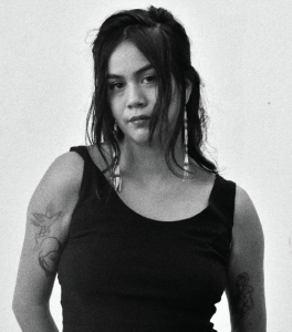 b&w photograph. Paisley Nahanee is centered and wearing a black tank top revealing a delicate tattoos on both her upper arms. her right shoulder is slightly raiser and her hair and a pair of long beaded earrings framer her face and hit her collar bones. her hair is parted down the middle and is pulled back from her face in a half-up half-down style with waved bangs covering her cheeks. her head is tilted slightly down and to the left. she makes direct eye contact with the viewer. very mona lisa esque.