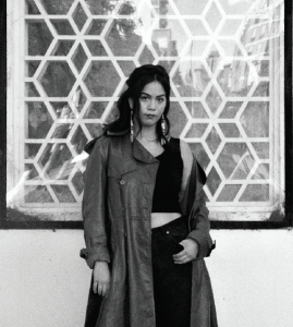 Paisley Nahanee stands in front of a window with a strong geometric design. she is wearing a black tank top, black jeans, and a brown leather trench coat. the coat is shrugged off her left shoulder and her left hand rests on her jean pocket. her head is tilted slightly down and to the right. her dark hair is in a half-up-half-down style with wavy bangs and long beaded earrings framing her cheeks.