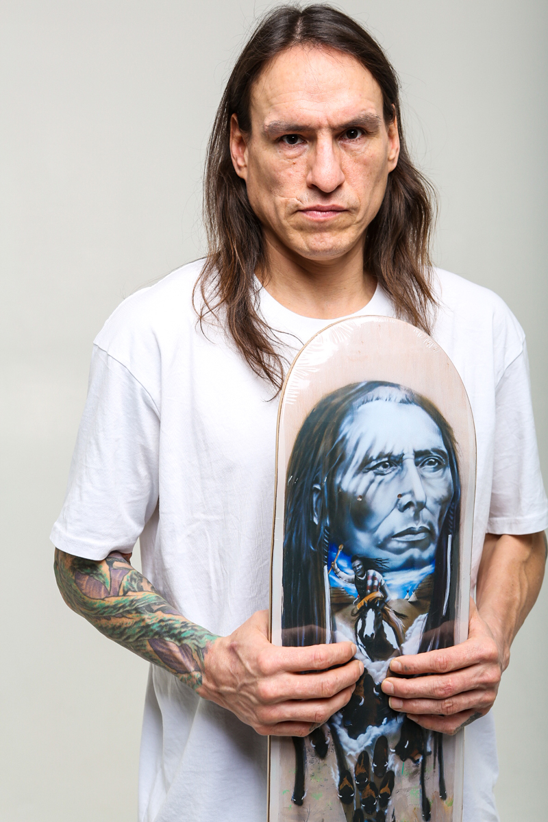 portrait photo of Joe Buffalo holding his Pitikwahanapiwiyin (Poundmaker) pro-model board.