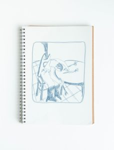 a sketchbook with an illustration of a person in cowboy boots sitting in a chair with their head on the round table next to them. there are two flowers on the table.