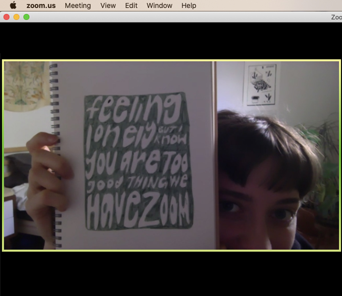 "screenshot off of a Zoom video call where Julia is holding up her sketchbook with an illustration that says ""feeling lonely but I know you are too good thing we have Zoom""."