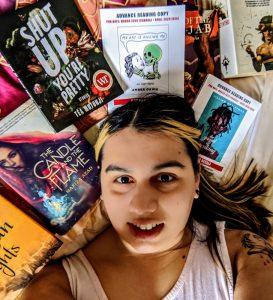 selfie image of Serena Bhandar lying down amongst books
