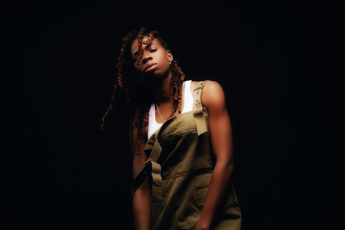 portrait photo of Haviah Mighty standing in front of a black backdrop in a white tank top and olive green overalls by Yung Yemi