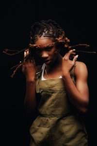 portrait photo of Haviah Mighty with her hair in motion around her in front of a black backdrop by Yung Yemi