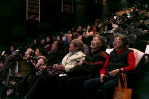 photo from the Speak My Language Launch of the audience, with the Chinese seniors sitting in the front row listening, watching, laughing.
