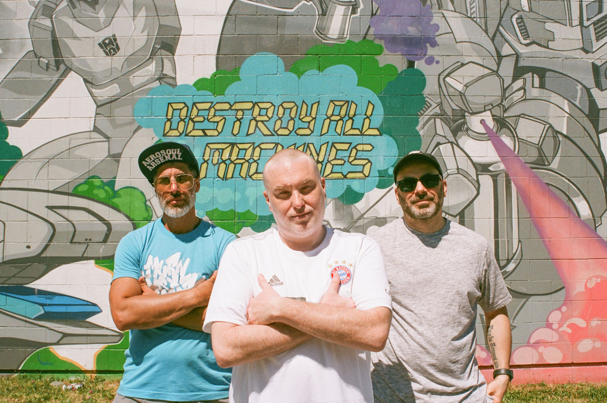 portrait photo of (from left to right) Dedos, Jay Swing, and FlipOut standing in front of a mural done by the AA Crew.